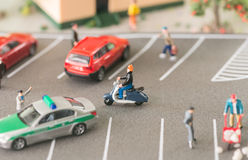 La vie urbaine occupée avec les personnes et les automobiles miniatures sur une rue passante photo stock