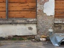 La vieille barrière détruite de brique avec des boucliers des lamelles en bois est une couleur brune chaude, près des chiffons de Photographie stock