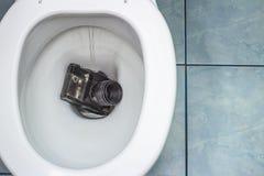 La vieille caméra de film enfoncée dans la toilette images stock