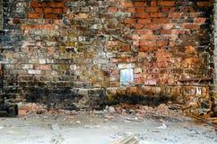 La vieille combustion de mur, détruit avec une petite fenêtre Des restes des briques cassées sur un plancher ainsi que des déchet Images stock