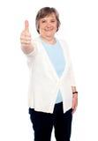 La vieille dame de sourire affichant des pouces lèvent le geste Photographie stock libre de droits