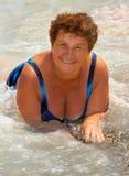 La vieille dame heureuse sur une plage, dans l'eau images libres de droits