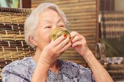 La vieille dame a posé confortablement à la maison boire une tasse de café image stock