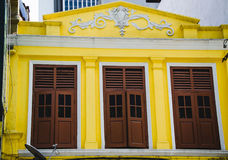 La vieille façade jaune de bâtiment avec trois volets et le stuc fonctionnent Architecture de ville Patrimoine culturel Image stock