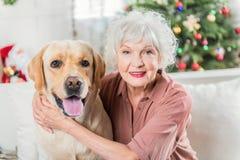 La vieille femelle gaie pose avec son Labrador Image stock