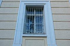 La vieille fenêtre derrière le fer râpant sur un mur en béton brun images libres de droits