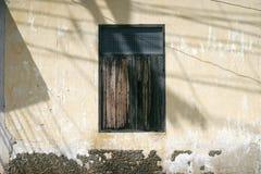 La vieille fenêtre en bois sur le mur antique de ciment avec la lumière et l'ombre, vintage bleu a filtré l'image Photo libre de droits
