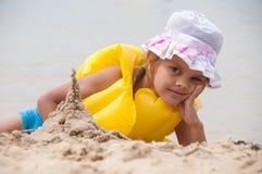 La vieille fille de cinq ans sur le sable de plage a construit la tour Photo stock
