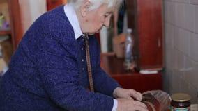 La vieille grand-mère dans la cuisine banque de vidéos