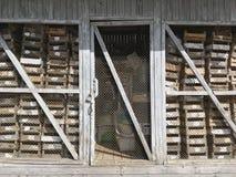 La vieille grange en bois avec la porte fermée et vident les caisses en bois Photographie stock