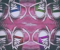 La vieille jeunesse a coloré des espadrilles sur la vieille surface en bois rose, vue supérieure Image libre de droits
