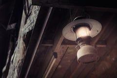 La vieille lampe à pétrole sale accrochante modifient selon la lampe électrique dans le style de film de vintage Photographie stock libre de droits