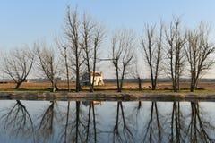 La vieille maison derrière les arbres s'est reflétée en rivière Images libres de droits