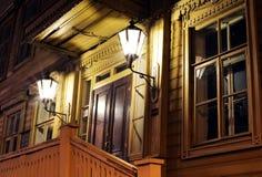 La vieille maison en bois russe de vintage à la lumière de la nuit s'allume Image libre de droits