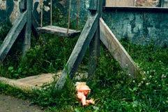 La vieille oscillation cassée en bois La poupée en plastique oubliée dans une herbe image libre de droits