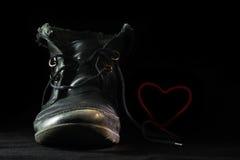 La vieille portée chaussure noire dans l'amour forme un coeur rouge de rougissement avec Photos libres de droits