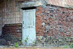 La vieille porte grise sur le mur d'une maison abandonnée de brique Images libres de droits
