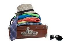 La vieille valise et les choses pliées là-dessus et les lunettes de soleil s'approchent de lui Photographie stock libre de droits