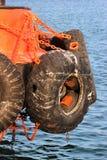 La vieille voiture d'occasion fatigue comme amortisseur sur un bord du navire Images stock