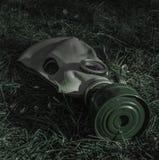 La vieja careta antigás soviética en la hierba en el abatimiento de la noche imagenes de archivo