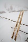 La vieja caza esquía con la piel en fondo de la nieve Fotografía de archivo