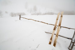 La vieja caza esquía con la piel en fondo de la nieve Fotos de archivo libres de regalías