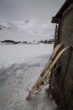 La vieja caza esquía con la piel en fondo de la nieve Foto de archivo libre de regalías
