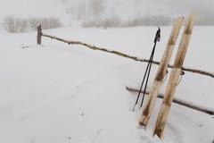 La vieja caza esquía con la piel en fondo de la nieve Foto de archivo