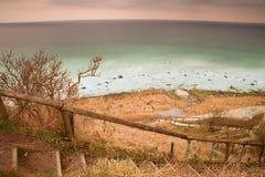 La vieja manera de madera de la escalera abajo con el hadrail de madera, reduce a la colina de la orilla de mar Foto de archivo