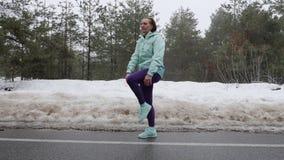 La vieja mujer cauc?sica mayor calienta estirar antes de correr en el parque nevoso del invierno Tiro lateral almacen de video