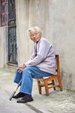 La vieja señora china se sienta afuera en una pequeña silla de madera, Yangzhou, China Fotografía de archivo