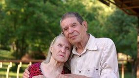 La viejos abuela y abuelo tristes están abrazando en parque metrajes