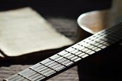 La vieux guitare et cahiers de musique se sont allumés par le soleil Image stock
