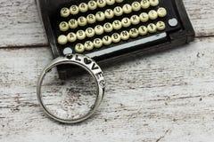 La vieux machine à écrire et anneau avec l'inscription aiment Photographie stock