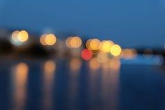 La ville brouillée s'allume avec l'effet de bokeh reflété sur la surface de l'eau Image stock