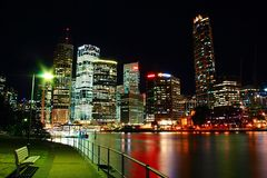 La ville de Brisbane par des réflexions colorées vertes rouges de rivière de Brisbane de nuit arrosent et des sièges de nightscap Image stock
