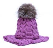La violeta hizo punto la bufanda y el sombrero de lana con el pompom aislado en el fondo blanco Imágenes de archivo libres de regalías