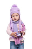 La violeta que llevaba sonriente linda de la niña hizo punto la bufanda y el sombrero, sosteniendo el regalo de la Navidad aislad Imagen de archivo libre de regalías