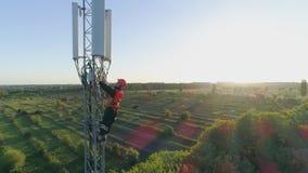 La visión aérea, hombre sonriente trabaja en torre de comunicación de la antena y muestra el pulgar para arriba en el fondo del p almacen de video