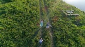 La visión aérea, muchacho alegre con las novias con las cintas coloreadas en manos corre en el prado a lo largo del río metrajes