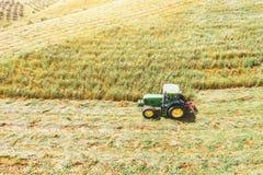 La visión aérea, tractor siega la hierba para la agricultura, alimentación del ganado adentro los campos, prados, colinas foto de archivo