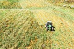 La visión aérea, tractor siega la hierba para la agricultura, alimentación del ganado adentro los campos, prados, colinas fotografía de archivo libre de regalías
