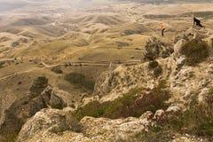 La visión desde arriba de la montaña al valle Los viajeros miran abajo Foto de archivo libre de regalías