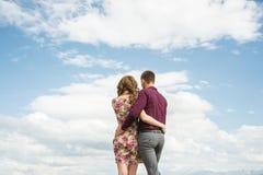 La visión desde detrás de un par joven se coloca en un abrazo y mira hacia fuera en la distancia contra el cielo con las nubes fotos de archivo libres de regalías