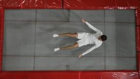 La visión desde el acróbata superior del gimnasta vestido en blanco realiza una voltereta en el trampolín almacen de video