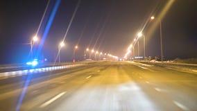 La visión desde el coche a través del parabrisas del coche en la pista de la noche con la iluminación de las lámparas Carretera d almacen de metraje de vídeo