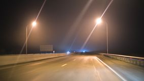 La visión desde el coche a través del parabrisas del coche en la pista de la noche con la iluminación de las lámparas Carretera d metrajes