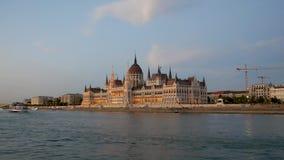 La visión desde el río Danubio al parlamento en Budapest por la tarde iluminó metrajes