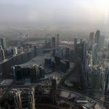 La visión desde el rascacielos abajo en la ciudad en la puesta del sol en Dubai Imágenes de archivo libres de regalías
