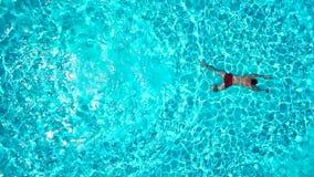 La visión desde el top como hombre se zambulle en la piscina y nada debajo del agua